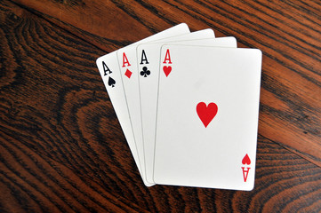 Four Aces - Playing Cards on Wooden Table