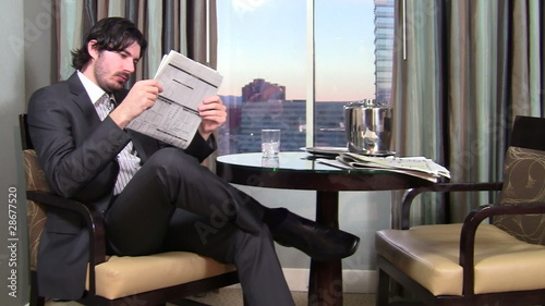 Businessman reads paper in hotel room - HD
