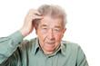 Alter Mann kratzt sich verlegen am Kopf