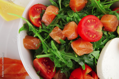 salad with smoked salmon in white bowl
