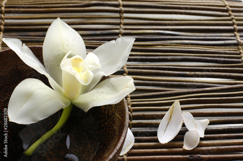 Fototapeta bowl of orchid, petal on bamboo mat