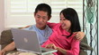 Young Asian couple working on laptop
