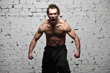 Strong muscular man stay in rage roar at white brick wall