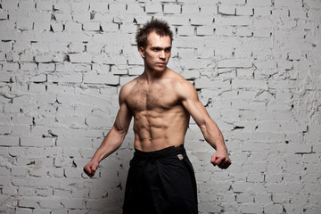 Strong muscular man stay  at white brick wall