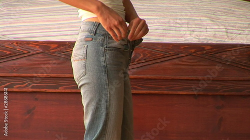 Young woman pulling up jeans
