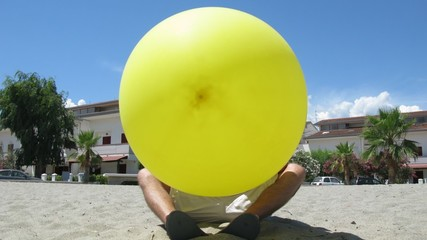The man sits on beach and inflates ball in Mandatoriccio, Italy.