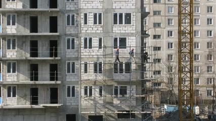 House building, builders build scaffolding