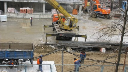 Work on building site: workers, crane, plates