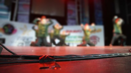 focus on wires of audio equipment on floor of stage