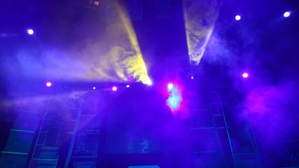 moving disco searchlights in smoke on stage of nightclub