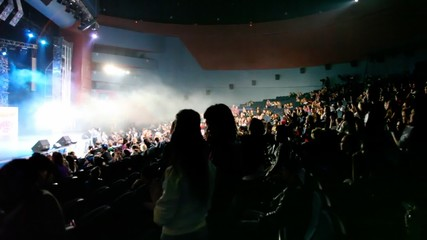 silhouettes of people applauds during youth concert