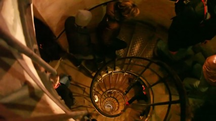 people ascending narrow spiral staircase in old building