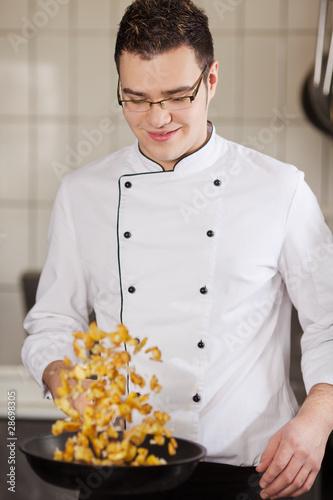 koch wendet bratkartoffeln in der pfanne