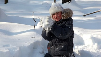 boy walks and plays snowballs in winter wood
