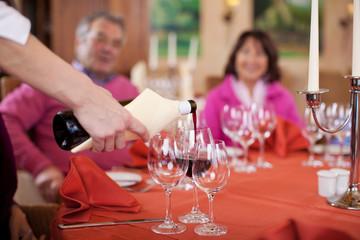 kellnerin schenkt gästen  rotwein ein