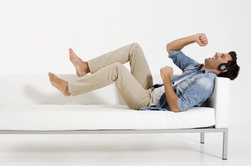 man on the couch listening music with headphones