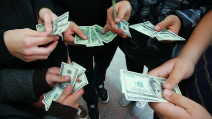 hands of men recount number of dollars and show closer to camera