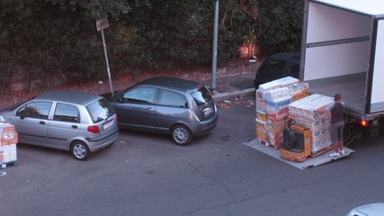 men load some cargo on truck with pallet jack  in Rome, Italy.