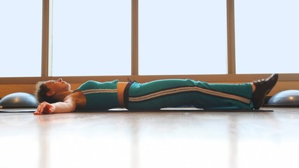 fitness woman lying and raising leg in gym