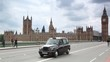 People, cars moving on Westminster Bridge, Big Ben in London