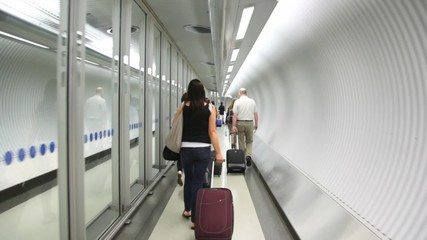 Back view of walking people with bags on escalator