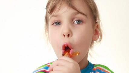 little girl licking lollipop in chicken form