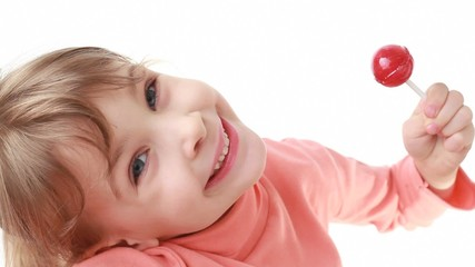 smiling little girl looks at camera and eating lollipop