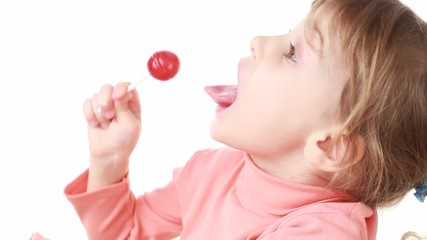 little girl eating lollipop, then looks at camera