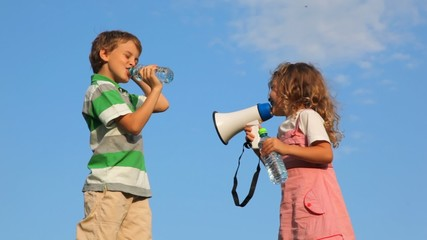 girl laughing through megaphone, boy drinking water