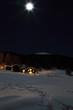chalet montano con neve e luna piena