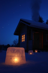 Log cabin in winter night with ice lantern decoration