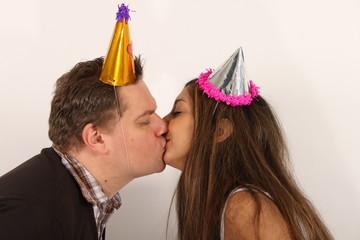 Ein Pärchen küsst sich auf einer Party