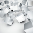 Falling and hitting gray metallic cubes on a white