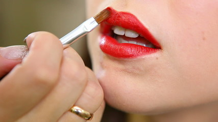 applying bright red lipstick on her lips young girl.