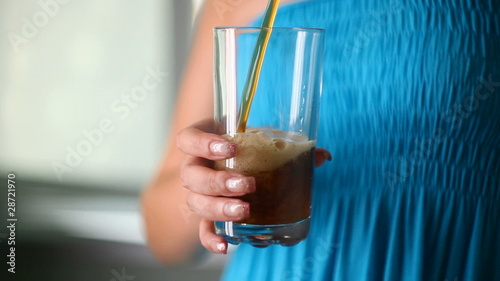 Girl is poured into a glass of fizzy lemonade.