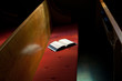 Open Bible Lying on Church Pew in Narrow Sunlight Band - 28723760