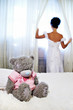 Bride near window and teddy bear on white bed