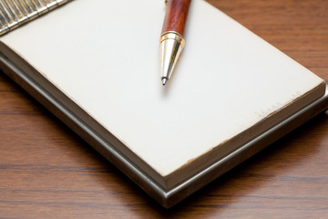 Elegant pen lying on a notebook on a wooden table