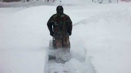 Blizzard man using snow blower away