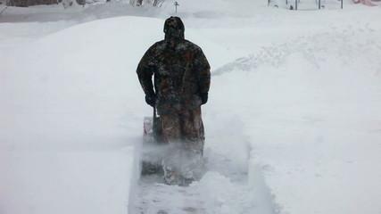 Blizzard man using snow blower away