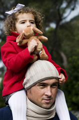 Man walking with young child on shoulders