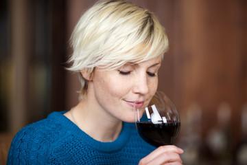 junge blonde frau genießt rotwein