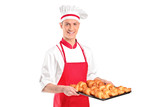 A baker with red apron holding croissants poster