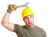 Bauarbeiter haut mit Schraubenschlüssel auf Helm