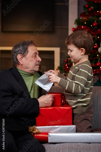 Small boy getting christmas present from grandfather