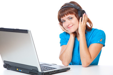 a girl with a laptop is listening to the music