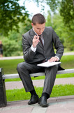 business man working with papers at park. Student