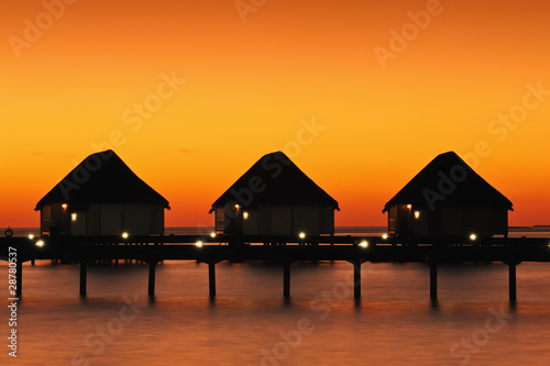 Tropical sunset with water villas