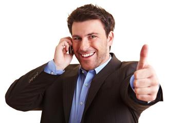 Telefonierender Mann hält Daumen hoch