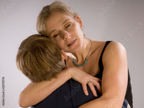 Mother hugging her son, sad and emotional
